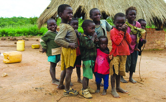 Children standing in front of a home in a village in Africa